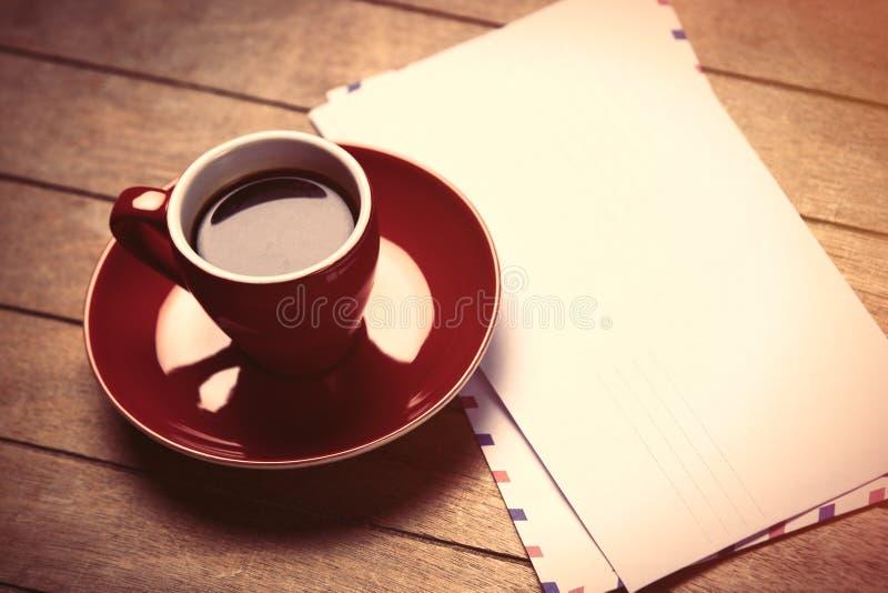 Foto des roten Tasse Kaffees und einiger Umschläge auf dem wonderfu stockfotografie
