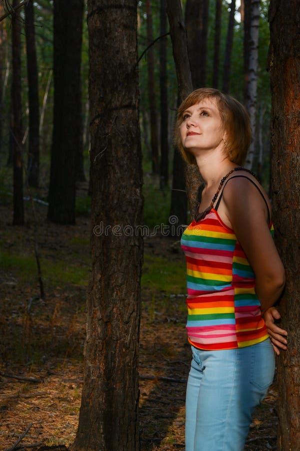 Foto des schönen Sitzes der jungen Frau unter dem Baum stockfotografie