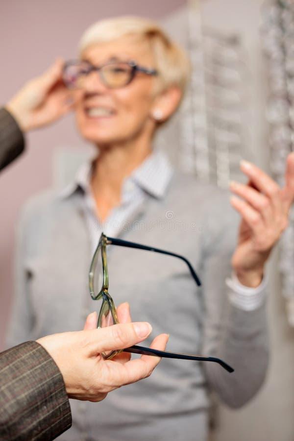 Foto des selektiven Fokus einer reifen Frau, die Brillen hält stockfoto