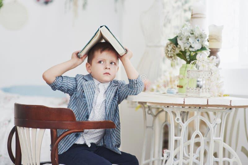 Foto des sorgfältigen Schülers mit Buch auf seinem Kopf, der Hausarbeit tut Der Schüler ist vom Handeln von Hausarbeit müde stockfotos