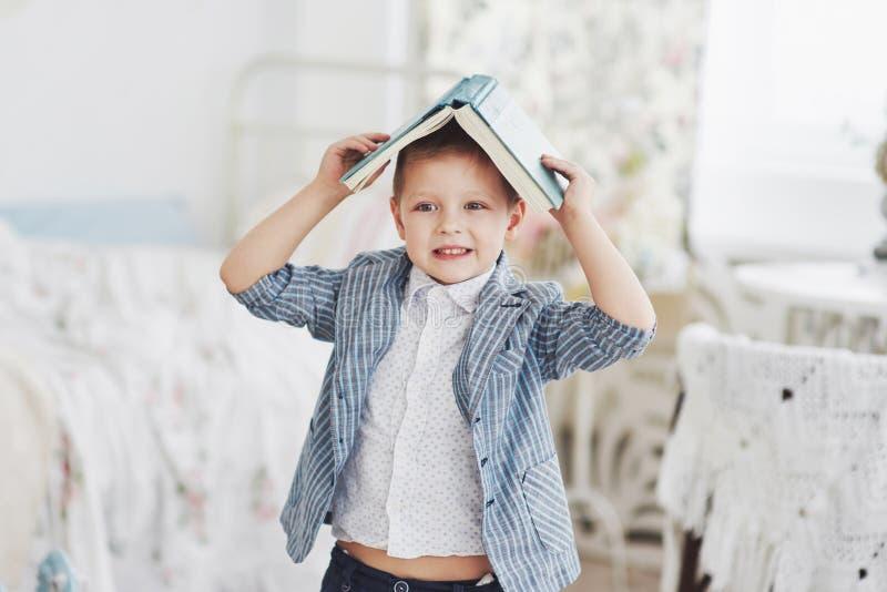 Foto des sorgfältigen Schülers mit Buch auf seinem Kopf, der Hausarbeit tut Der Schüler ist vom Handeln von Hausarbeit müde lizenzfreie stockfotos