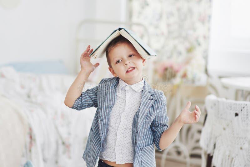 Foto des sorgfältigen Schülers mit Buch auf seinem Kopf, der Hausarbeit tut Der Schüler ist vom Handeln von Hausarbeit müde stockfoto