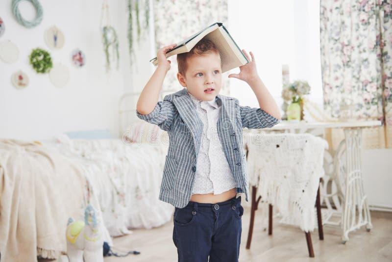 Foto des sorgfältigen Schülers mit Buch auf seinem Kopf, der Hausarbeit tut Der Schüler ist vom Handeln von Hausarbeit müde stockbild