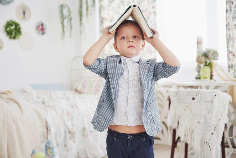 Foto des sorgfältigen Schülers mit Buch auf seinem Kopf, der Hausarbeit tut Der Schüler ist vom Handeln von Hausarbeit müde lizenzfreies stockfoto