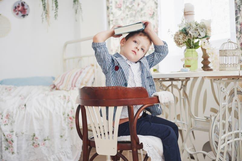 Foto des sorgfältigen Schülers mit Buch auf seinem Kopf, der Hausarbeit tut Der Schüler ist vom Handeln von Hausarbeit müde stockfotografie