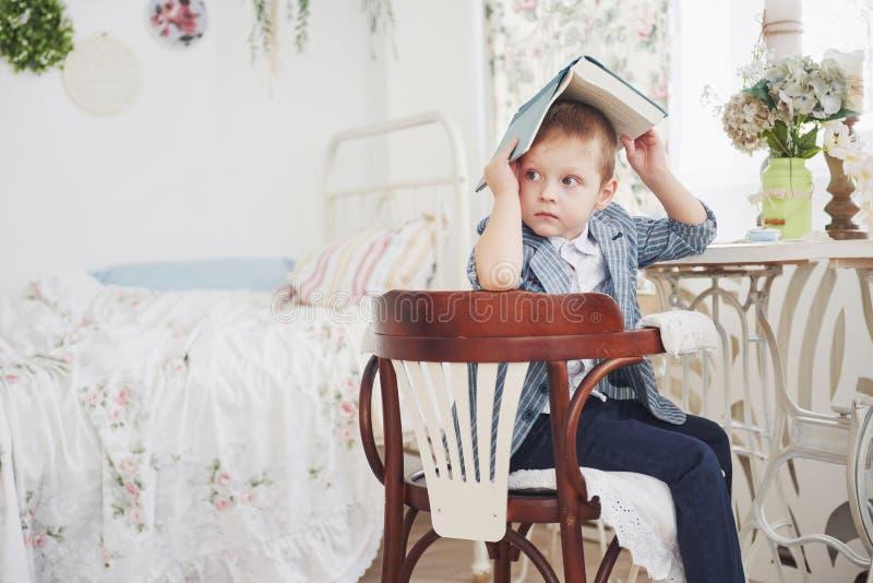 Foto des sorgfältigen Schülers mit Buch auf seinem Kopf, der Hausarbeit tut Der Schüler ist vom Handeln von Hausarbeit müde lizenzfreie stockfotografie
