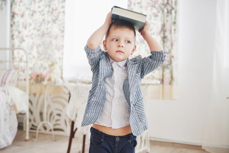Foto des sorgfältigen Schülers mit Buch auf seinem Kopf möchte nicht studieren und gehen zu schulen Der Schüler ist von müde lizenzfreie stockfotografie