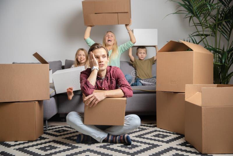 Foto des umgekippten Mannes sitzend auf Boden und der Frauen mit dem Jungen und Mädchen, die auf grauem Sofa sitzen lizenzfreie stockbilder