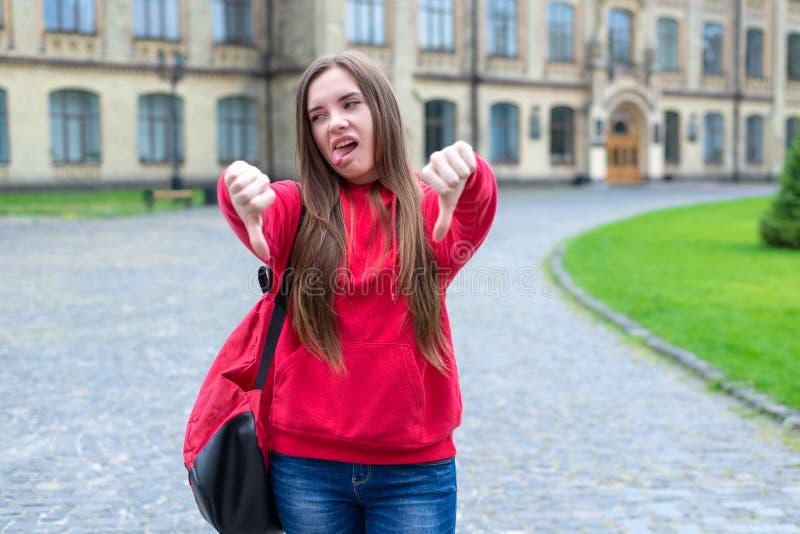Foto des verrückten Jugendlichen mögen nicht zur Universität gehen wünschen, die Finger hinunter Symbol zeigt lizenzfreie stockfotografie