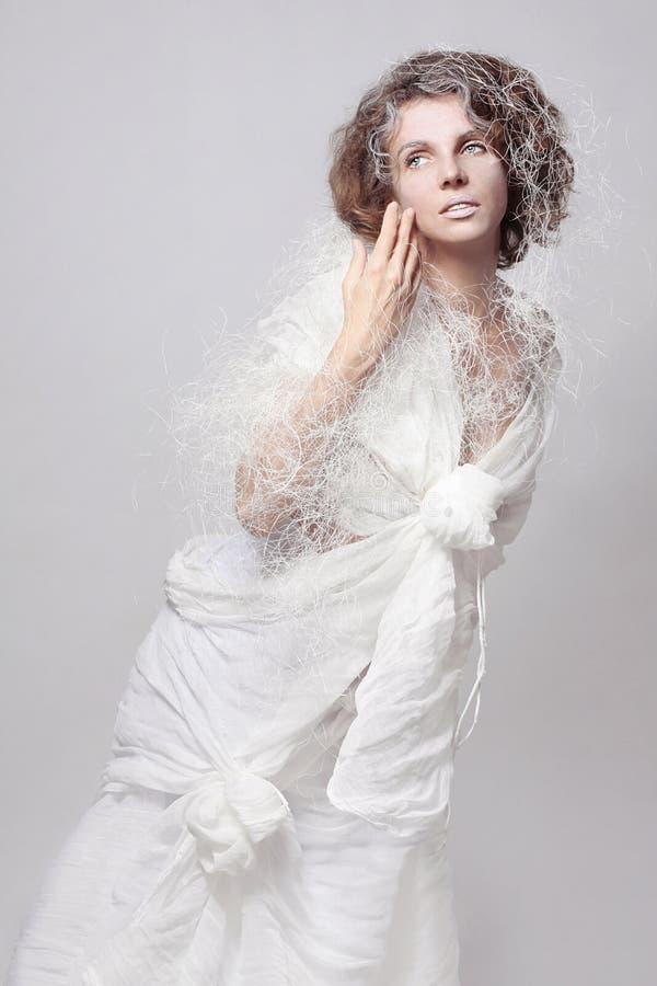 Foto di arte di una ragazza in un costume di alte mode di un vestito bianco operato dal cotone su un fondo bianco in isolamento fotografia stock libera da diritti
