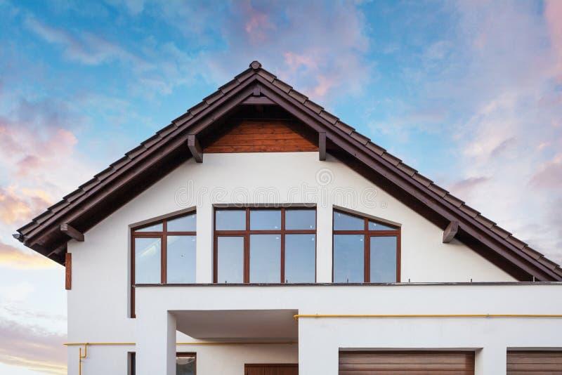 Foto di bella comodità e di nuova casa con le grandi finestre del tetto marrone e la parete bianca contro cielo blu calmo fotografia stock