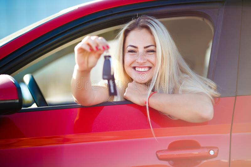 Foto di bella donna bionda con le chiavi che si siedono in automobile rossa con la finestra aperta fotografie stock libere da diritti