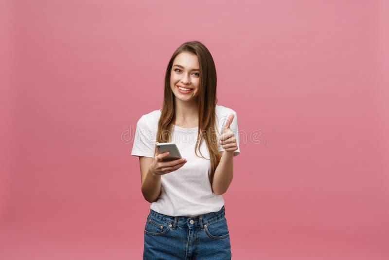 Foto di bella giovane donna sveglia allegra che chiacchiera dal telefono cellulare isolato sopra il fondo rosa della parete immagine stock