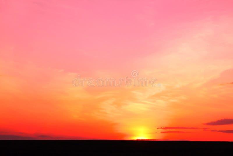 Foto di bello tramonto tropicale colorato rosso luminoso di estate in tempo leggermente nuvoloso piacevole fotografia stock libera da diritti