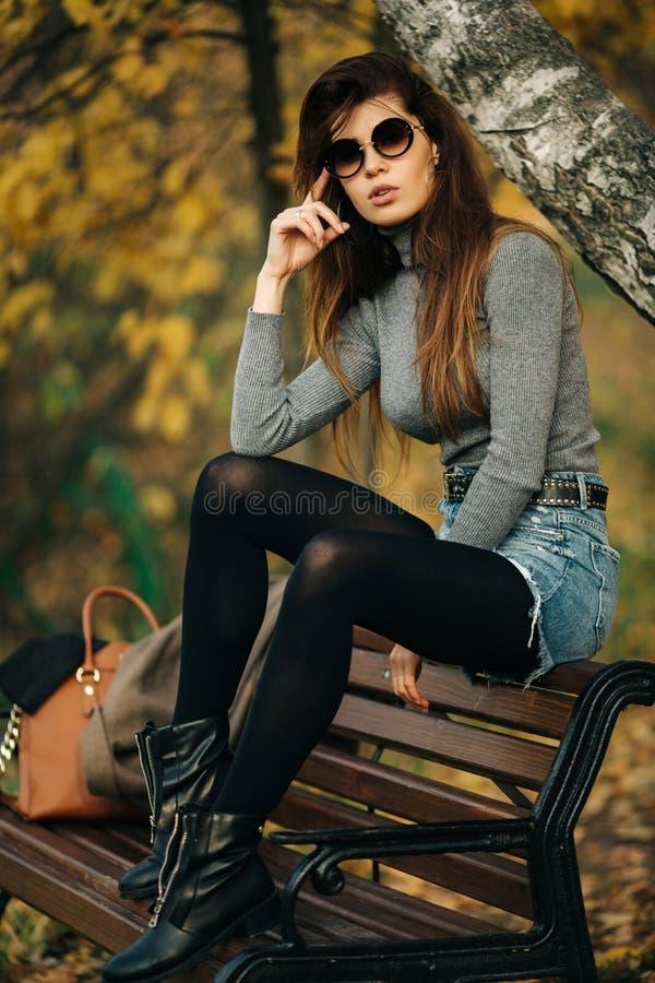 Foto di castana in occhiali da sole che si siedono sul banco nel parco di autunno fotografia stock