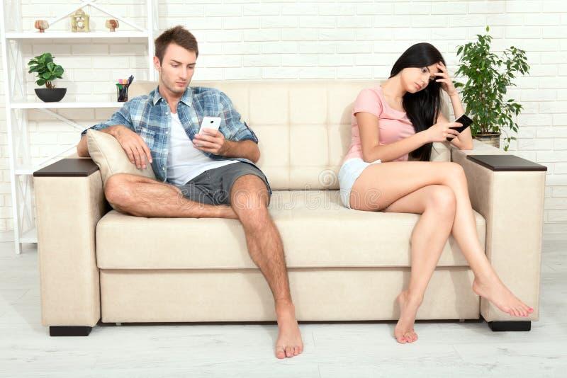 Foto di concetto di dipendenza dello smartphone la giovane donna e l'uomo che si siedono sul sofà con lo smartphone e fanno non e fotografia stock