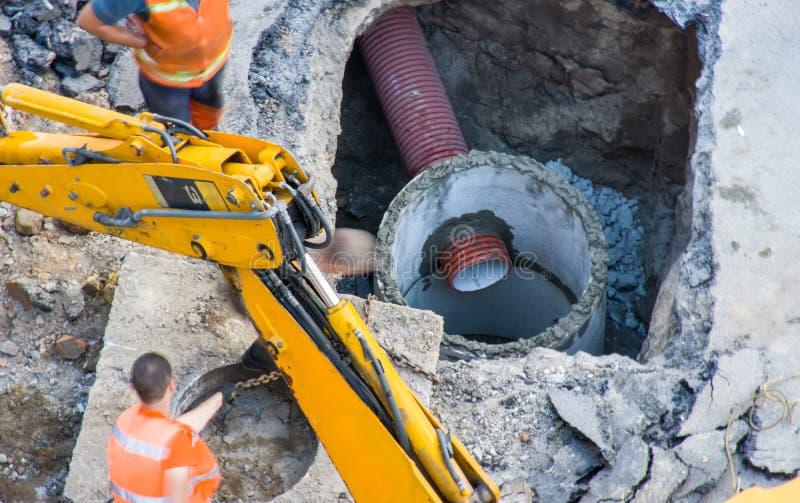 Foto di costruzione o del rifornimento idrico attivo di riparazione, fogna o rete fognaria del tubo in pozzo concreto dai lavorat fotografia stock libera da diritti