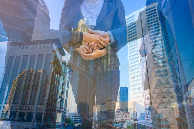 Foto di doppia esposizione La città della costruzione della miscela della foto e stringe le mani fotografie stock
