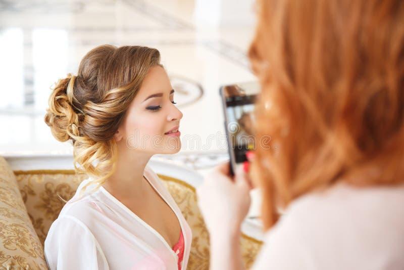 Foto di fabbricazione alla moda dei capelli e del truccatore di bella sposa sul suo smartfone immagini stock