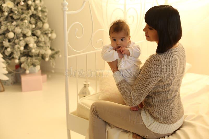 Foto di festa bella madre che posa con il suo piccolo bambino sveglio fotografia stock libera da diritti
