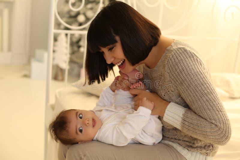 Foto di festa bella madre che posa con il suo piccolo bambino sveglio fotografia stock