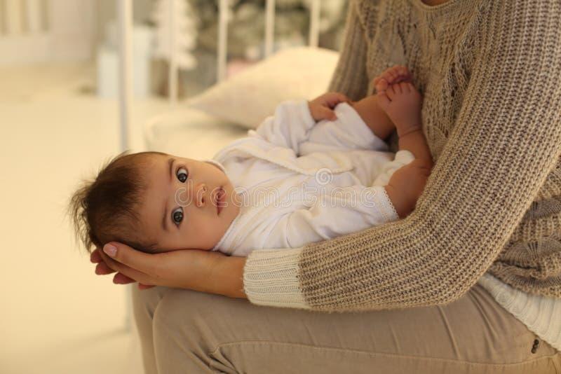 Foto di festa bella madre che posa con il suo piccolo bambino sveglio fotografie stock