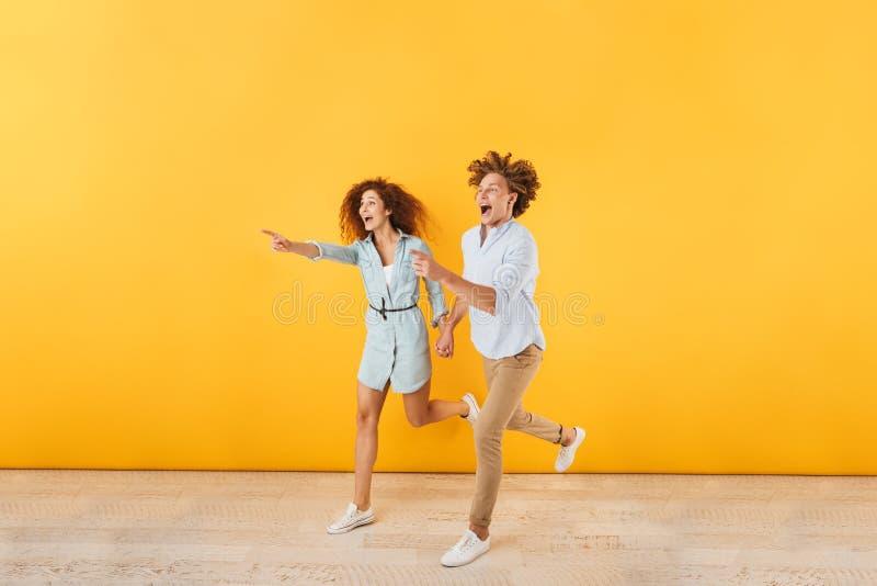 Foto di funzionamento felice della donna e del giovane 20s e di indicare fing fotografia stock libera da diritti