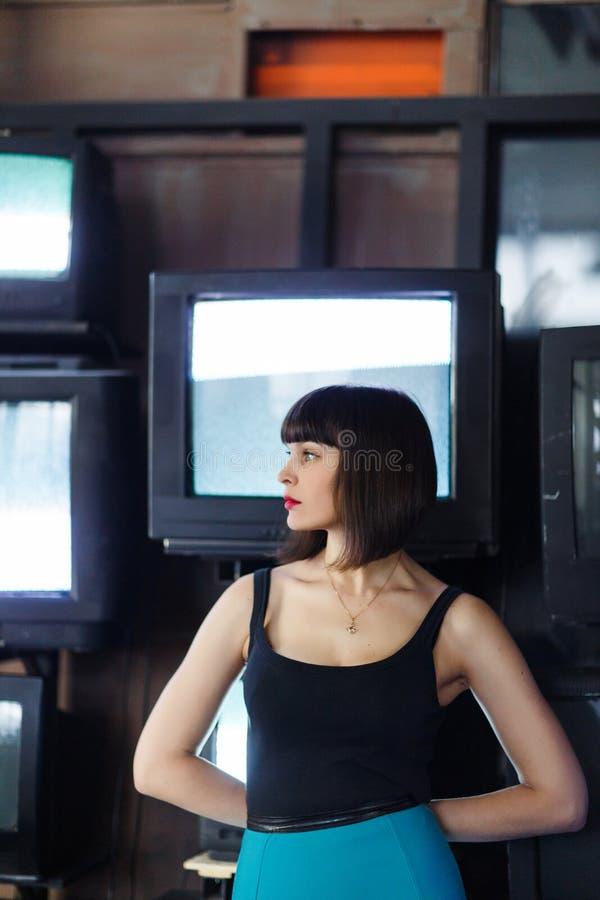 Foto di giovane castana sul fondo della parete con la TV fotografie stock libere da diritti