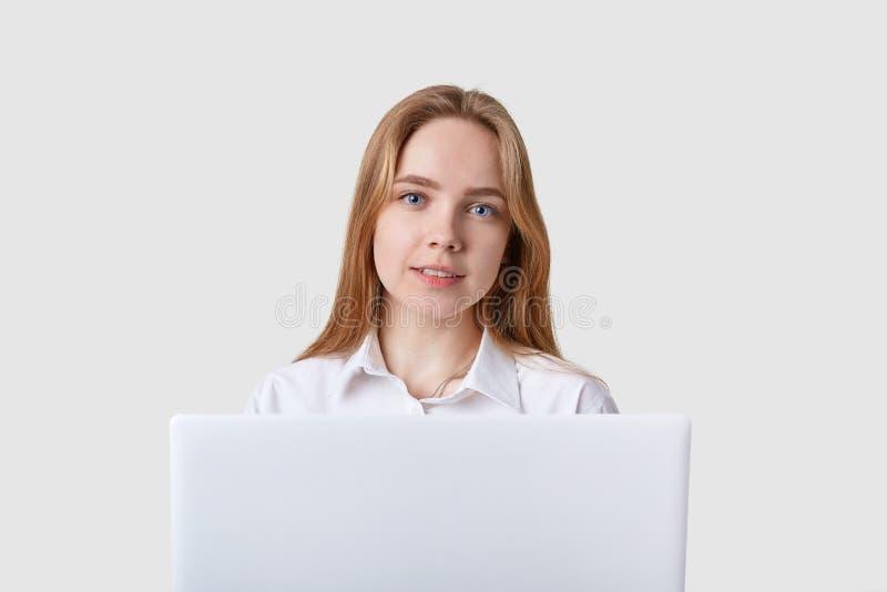 Foto di giovane donna allegra caucasica che si siede sopra la parete bianca con il computer lportable del aptop Esaminando dirett fotografia stock