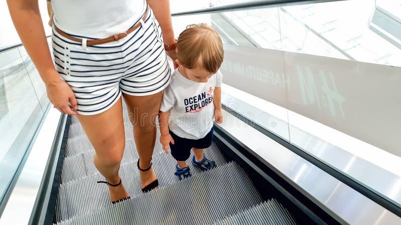 Foto di giovane madre che tiene a mano il suo piccolo figlio mentre guidando sulla scala mobile al centro commerciale fotografia stock