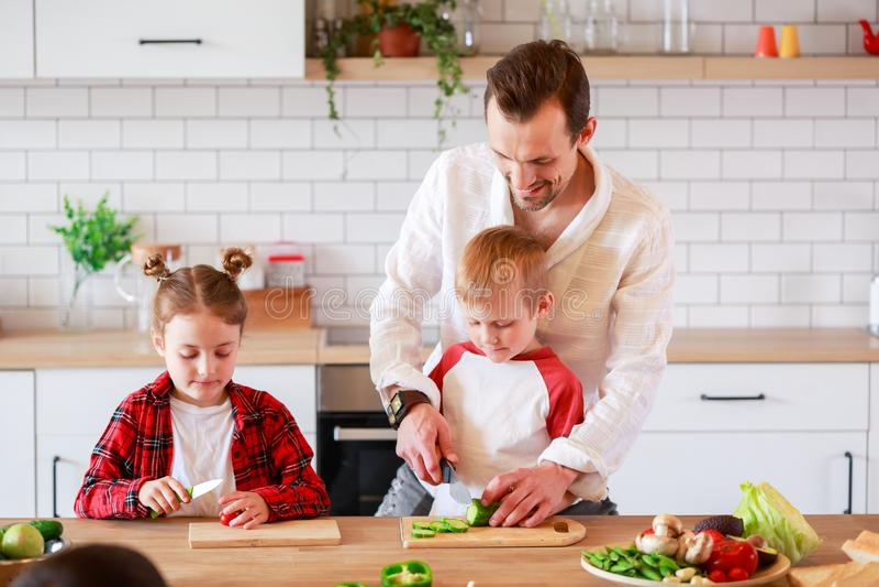 Foto di giovane padre con il derivato ed il figlio che cucinano alla tavola immagine stock libera da diritti