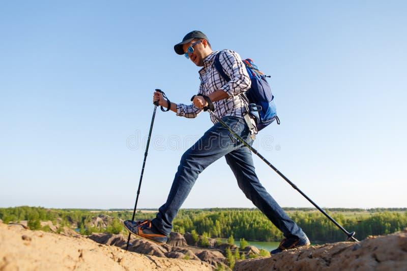 Foto di giovane uomo turistico con i bastoni da passeggio che cammina nell'area montagnosa fotografia stock