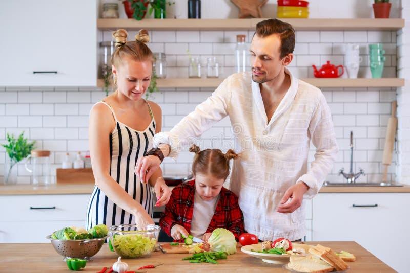 Foto di giovani genitori con la figlia che prepara alimento fotografia stock libera da diritti