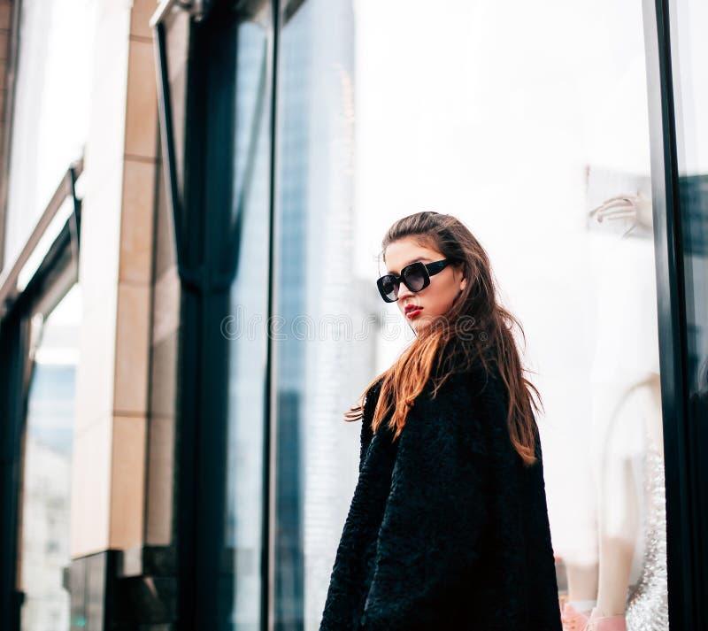 Foto di modo di bella giovane donna con gli occhiali da sole Looking di modello alla macchina fotografica Stile di vita della cit fotografia stock libera da diritti