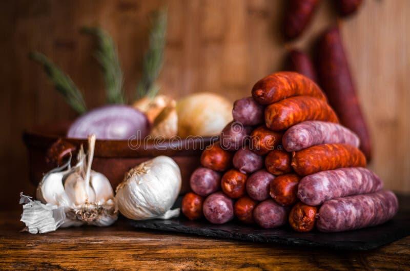 Foto di natura morta delle salsiccie piccanti bianche & rosse nel piramid del triangolo accanto ad aglio nella cipolla tradiziona fotografie stock libere da diritti