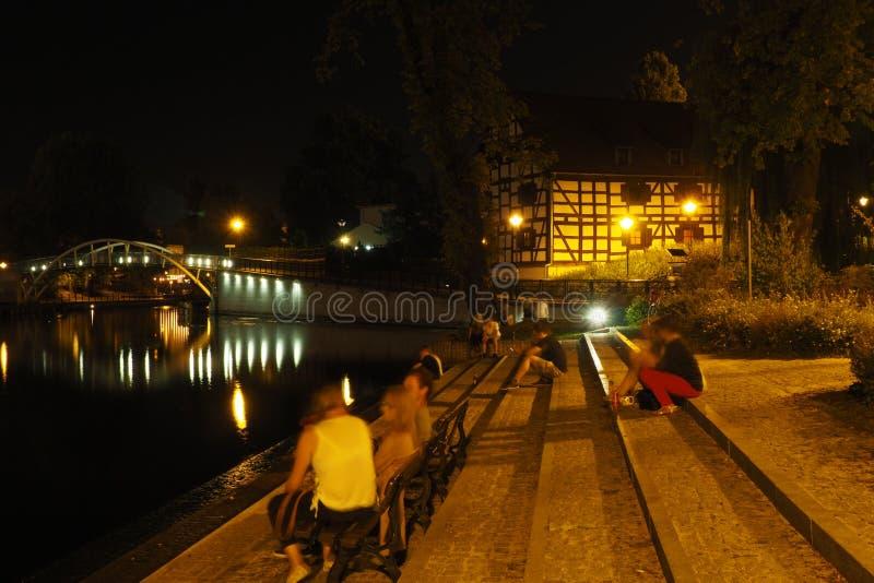 Foto di notte dei giovani che si siedono e che si rilassano sulle scale immagine stock