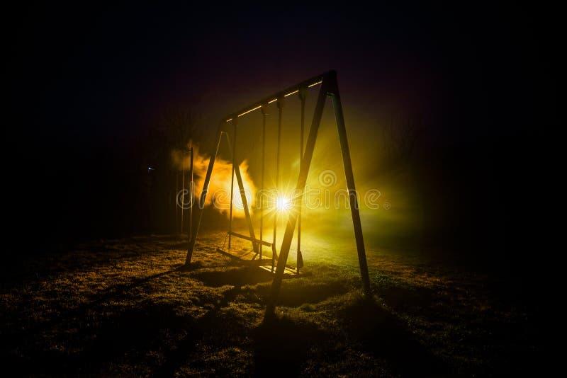 Foto di notte dell'oscillazione del metallo che sta all'aperto alla notte con nebbia e luce tonificata surreale su fondo Nessuno  immagine stock