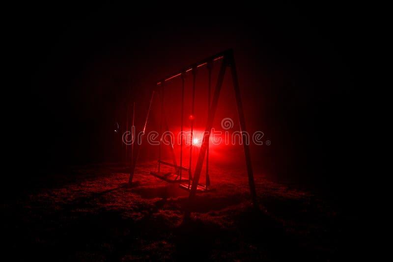 Foto di notte dell'oscillazione del metallo che sta all'aperto alla notte con nebbia e luce tonificata surreale su fondo Nessuno  fotografia stock