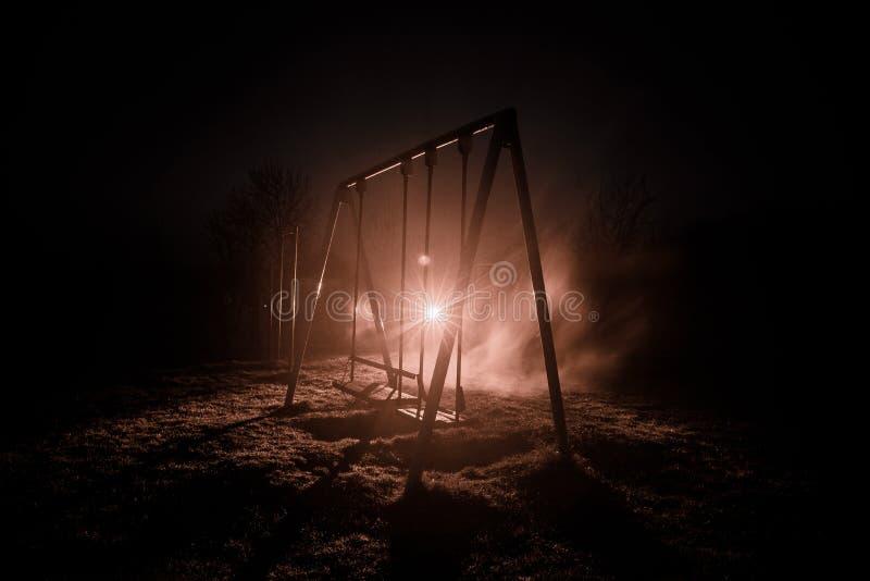 Foto di notte dell'oscillazione del metallo che sta all'aperto alla notte con nebbia e luce tonificata surreale su fondo Nessuno  fotografie stock