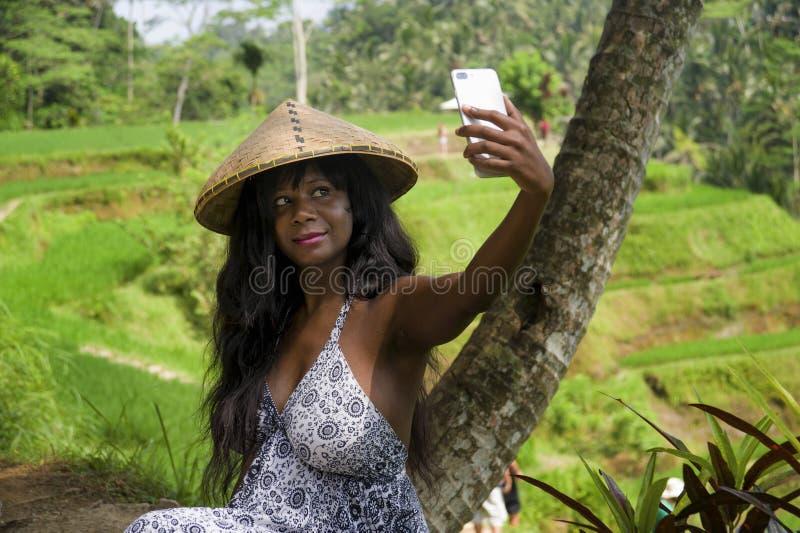 Foto di presa turistica del ritratto del selfie della giovane donna di colore afroamericana felice attraente con la macchina foto fotografie stock