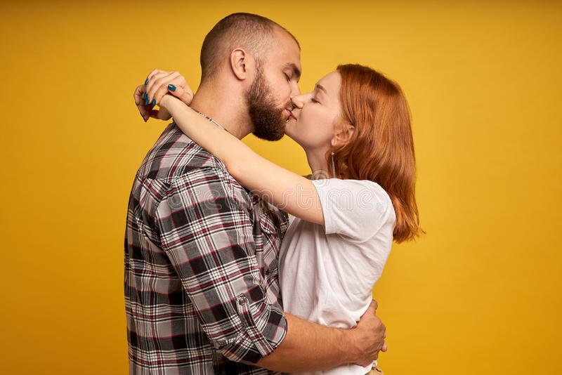 Foto di profilo di bei giovani nell'amore che esprime amore ed affetto mentre baciandosi con gli occhi chiusi isolati immagini stock