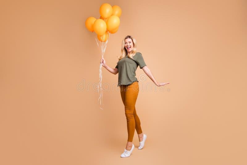 Foto di profilo a piena lunghezza di una graziosa ragazza bionda con molti palloncini d'aria color arancione, è arrivata la festa fotografia stock