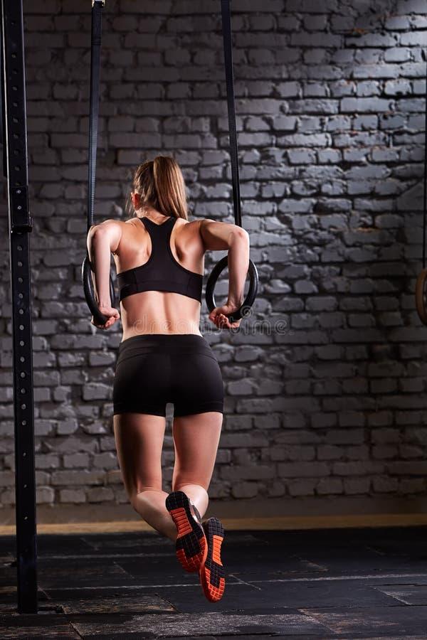 Foto di retrovisione di bella giovane donna sportiva nello sportwear nero che fa esercizio di tirata-UPS facendo uso degli anelli fotografia stock
