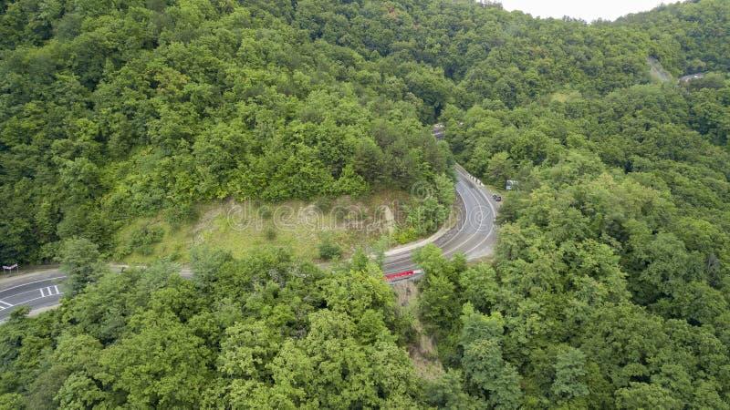 Foto di riserva aerea di guida di veicoli lungo la strada del passo di montagna di bobina attraverso la foresta in Soci, Russia fotografia stock