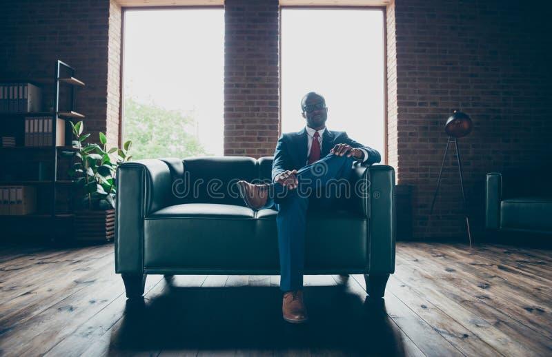 Foto di spec. di seduta di usura del sofà dell'ufficio del tipo macho scuro della pelle e del costume corporativo immagini stock libere da diritti