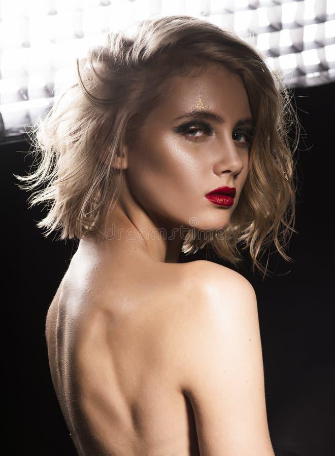 Foto di stile di modo e di arte di bella ragazza con capelli bagnati scompigliati, spalle nude, labbra rosse, posanti davanti all fotografia stock
