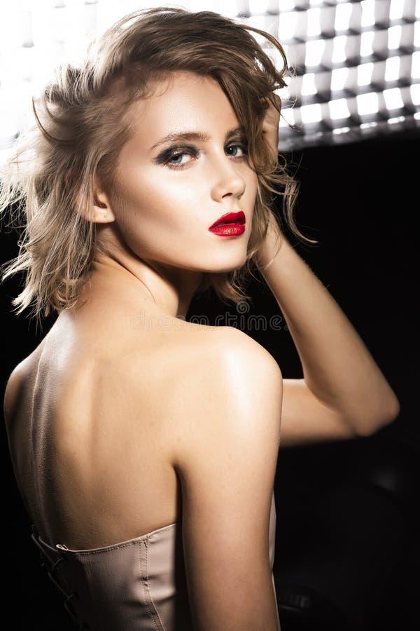 Foto di stile di modo e di arte di bella ragazza con capelli bagnati scompigliati, spalle nude, labbra rosse, posanti davanti all fotografie stock libere da diritti