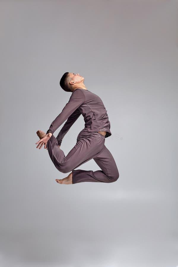 Foto di un ballerino di balletto atletico dell'uomo vestito in una tuta sportiva grigia, facente un elemento di ballo contro un f fotografia stock