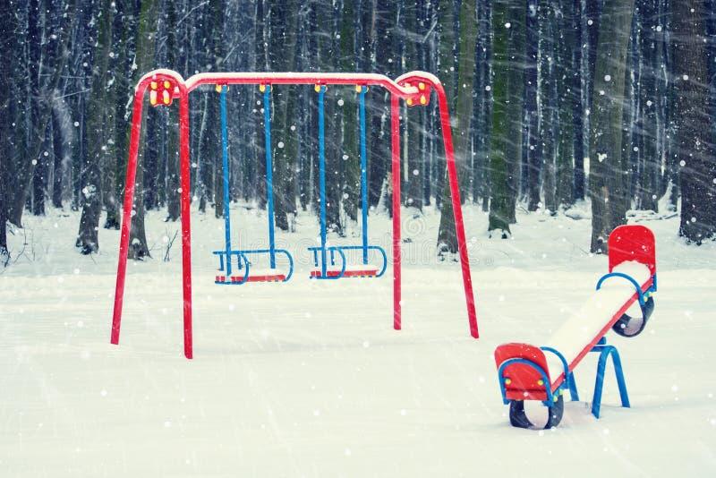Foto di un campo da giuoco in un parco nell'inverno con neve di caduta fotografie stock