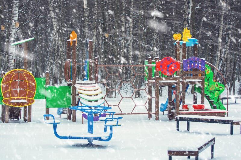 Foto di un campo da giuoco in un parco nell'inverno con neve di caduta immagine stock